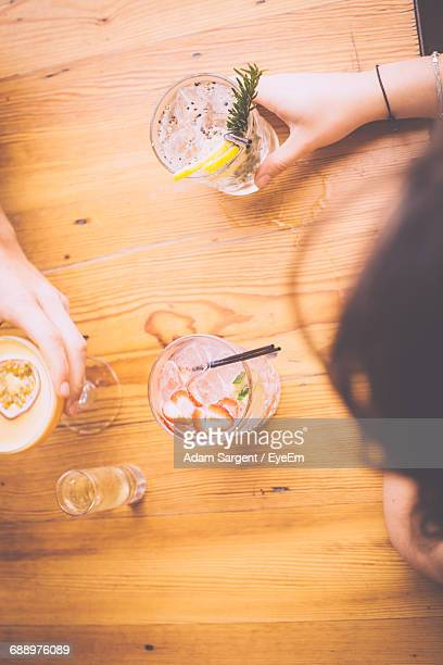 Cropped Image Of Friends Having Cocktail On Table