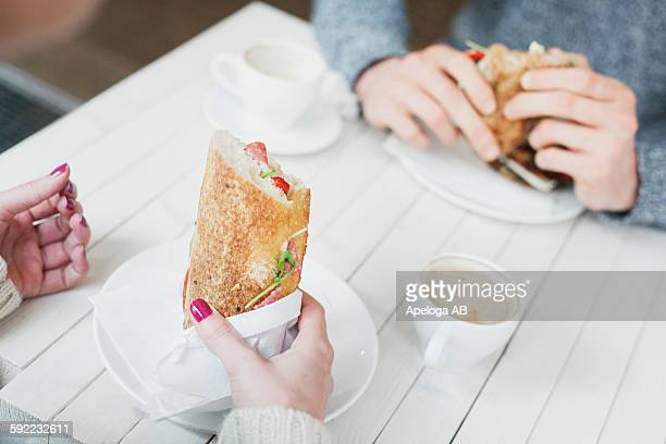 Cropped image of friends holding sandwiches at cafe table