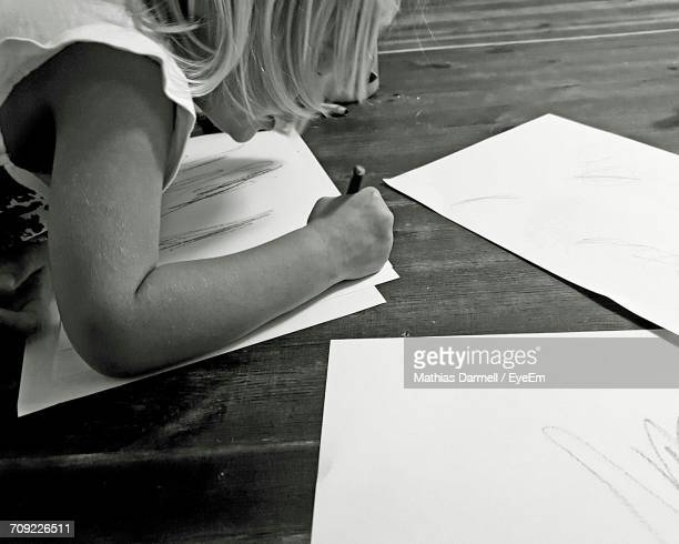 Cropped Image Of Girl Drawing On Paper