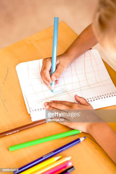 Cropped image of girl drawing with colored pencils in classroom