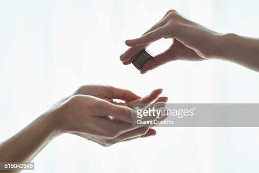 Cropped image of girl dropping coins in mother's hands