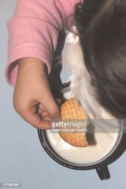 Cropped Image Of Girl Eating Biscuit With Milk At Home