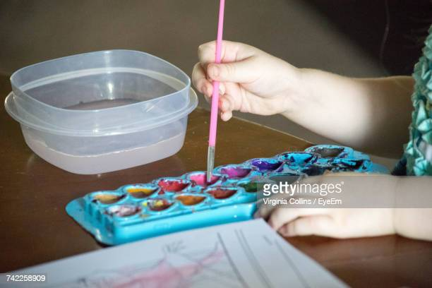 Cropped Image Of Girl Hand Putting Paintbrush In Palette On Table