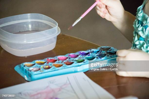 Cropped Image Of Girl Holding Paintbrush With Palette On Table