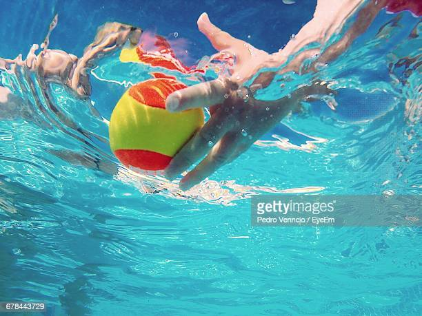 Cropped Image Of Girl Playing Ball In Swimming Pool