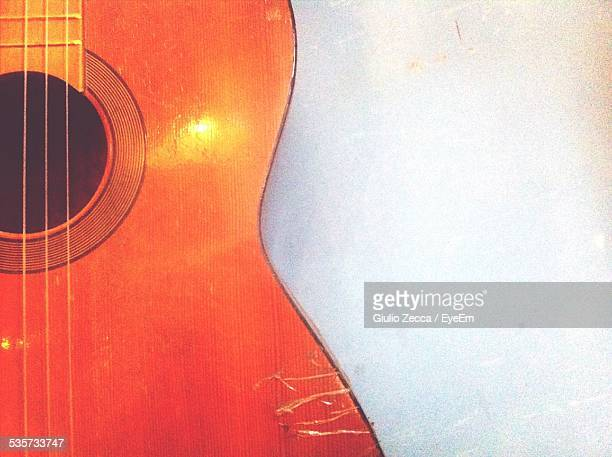 Cropped Image Of Guitar Leaning On White Wall