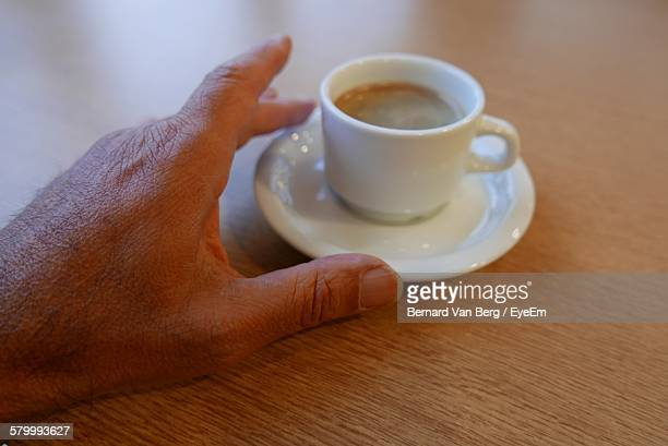 Cropped Image Of Hand And Coffee On Wooden Table