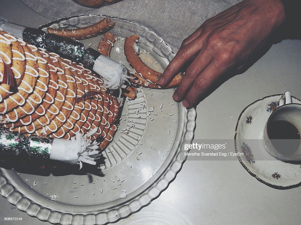 Cropped Image Of Hand By Kransekake In Plate On Table At Home