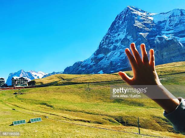 Cropped Image Of Hand By Snowcapped Mountain Against Sky