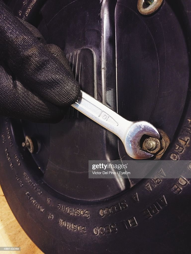 Cropped image of hand fixing bolt with wrench