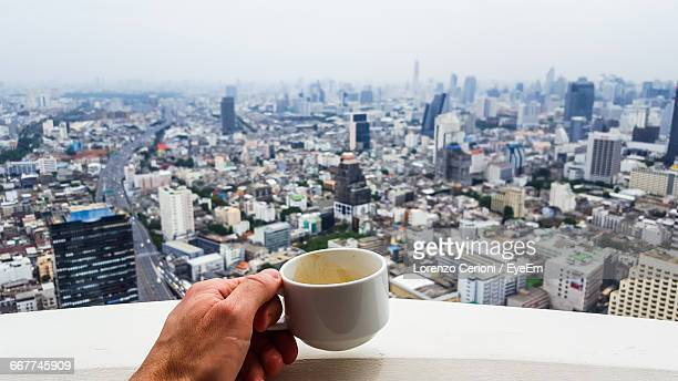 Cropped Image Of Hand Holding A Coffee Cup On The Balcony