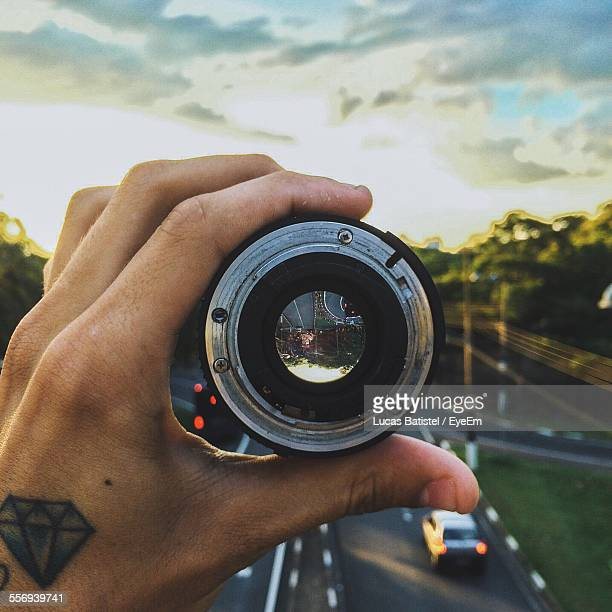 Cropped Image Of Hand Holding Camera Lens