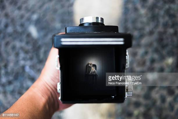 Cropped Image Of Hand Holding Camera