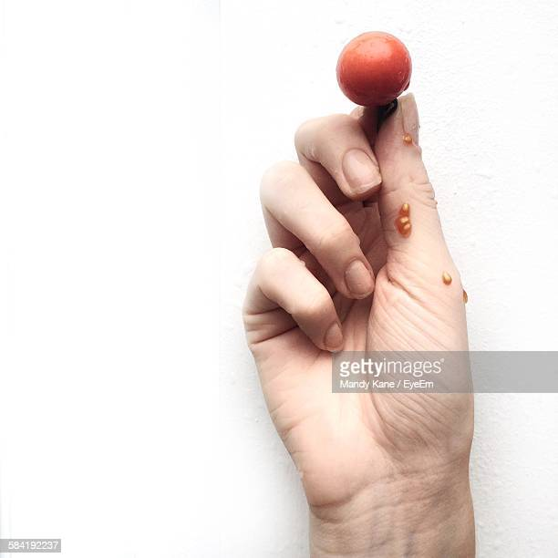 Cropped Image Of Hand Holding Cherry Tomato Against White Wall