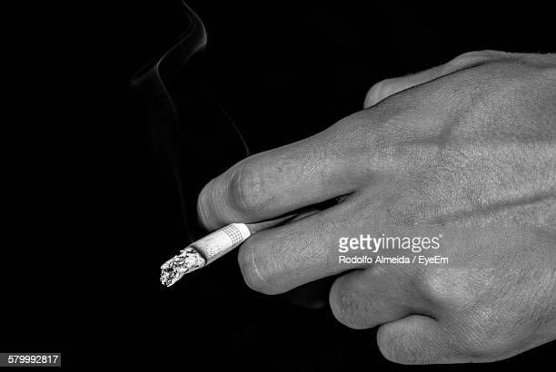 Cropped Image Of Hand Holding Cigarette Against Black Background