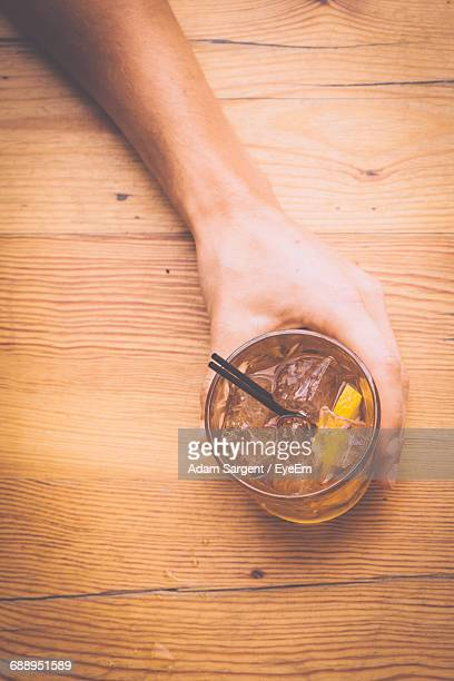 Cropped Image Of Hand Holding Cocktail On Table