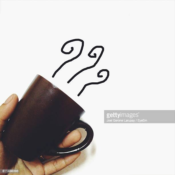 Cropped Image Of Hand Holding Coffee Cup Over Doodle On White Paper