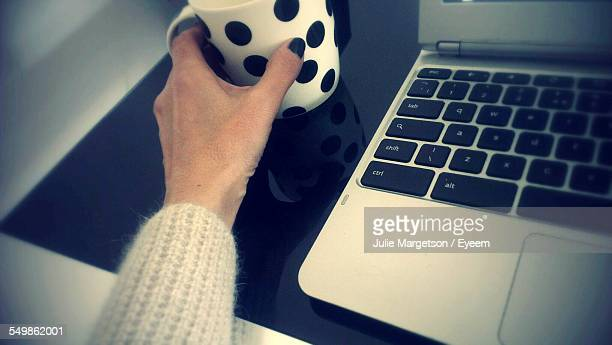 Cropped Image Of Hand Holding Coffee Mug By Laptop At Table