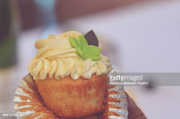 Cropped Image Of Hand Holding Cup Cake