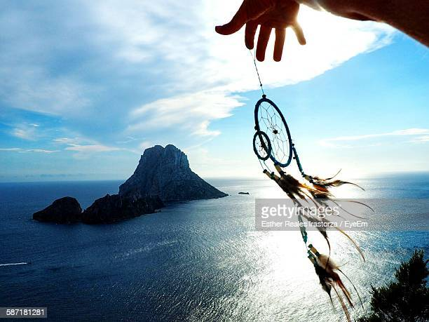 Cropped Image Of Hand Holding Dream Catcher Against Sea