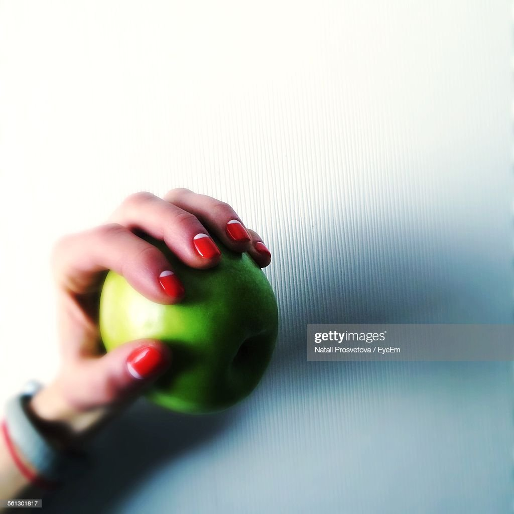 Cropped Image Of Hand Holding Granny Smith Apple Against White Wall