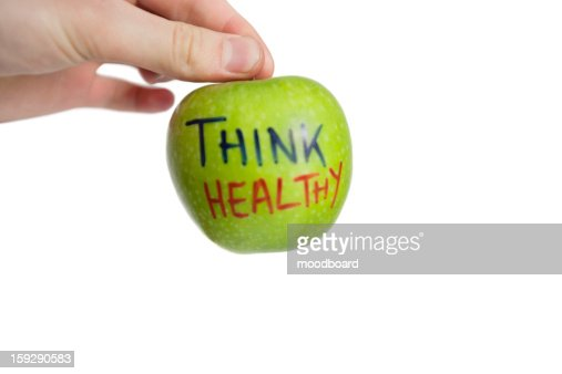 Cropped image of hand holding healthy granny smith apple over white background : Stock Photo