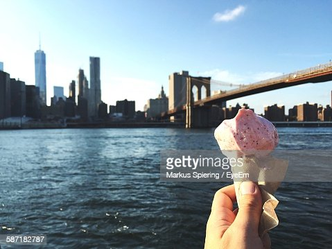 Cropped Image Of Hand Holding Ice Cream Against Brooklyn Bridge