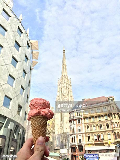 Cropped Image Of Hand Holding Ice Cream Cone Against St Stephens Cathedral