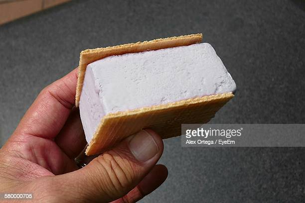 Cropped Image Of Hand Holding Ice Cream Sandwich On Street