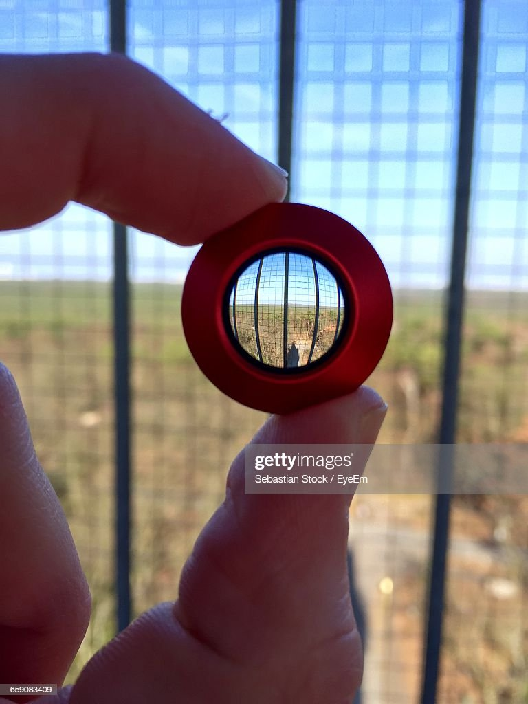 Cropped Image Of Hand Holding Lens Against Fence