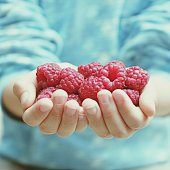 Cropped Image Of Hand Holding Raspberries