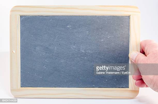 Cropped Image Of Hand Holding Slate Against White Background
