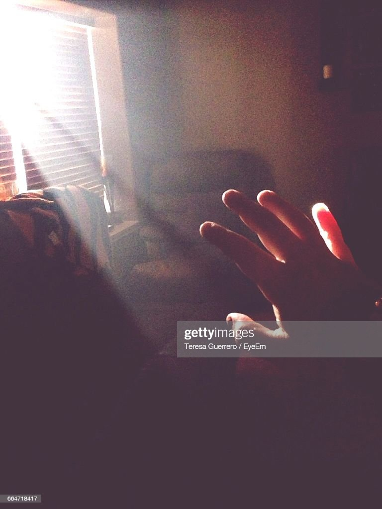Cropped Image Of Hand In Living Room Against Sunbeam