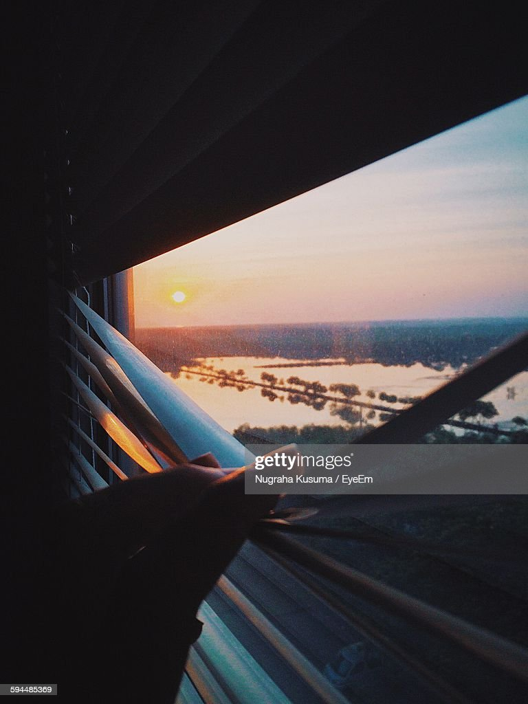 Cropped Image Of Hand On Window Blinds Against Sky During Sunrise