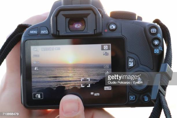 Cropped Image Of Hand Photographing Sunset Over Sea Through Dslr