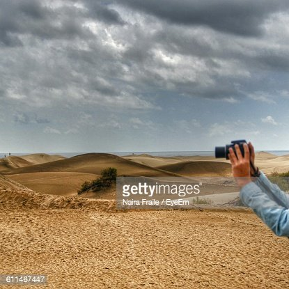 Cropped Image Of Hand Photographing Through Camera At Maspalomas Dunes
