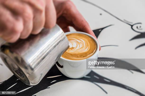 Cropped Image Of Hand Pouring Milk In Coffee Cup On Table