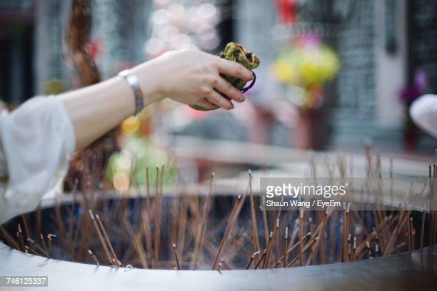 Cropped Image Of Hand Praying Over Incense