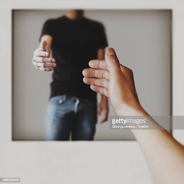 Cropped Image Of Hand Reaching Towards Photograph
