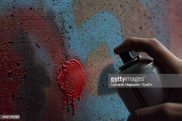 Cropped Image Of Hand Spraying Paint On Wall