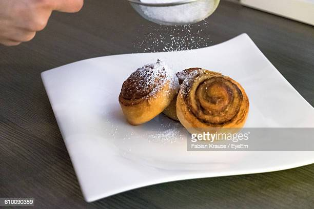 Cropped Image Of Hand Sprinkling Icing Sugar On Cinnamon Rolls At Table