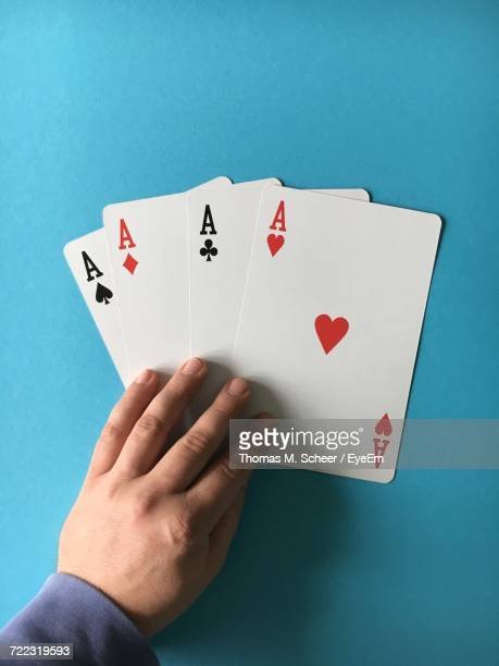 Cropped Image Of Hand With Aces Cards At Casino Table