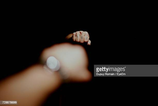 Cropped Image Of Hand With Tattoo Reflecting On Mirror In Darkroom