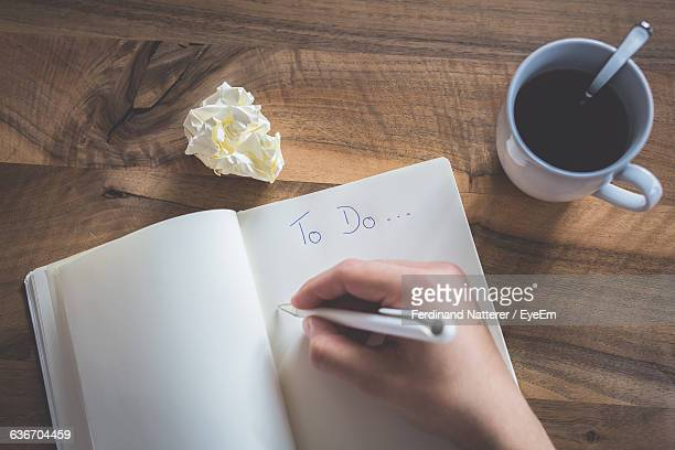 Cropped Image Of Hand Writing On Book By Coffee