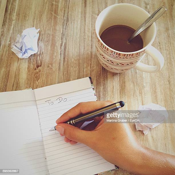 Cropped Image Of Hand Writing To Do List In Book On Table