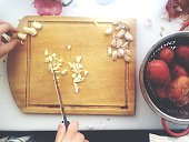 Cropped Image Of Hands Chopping Garlic On Cutting Board