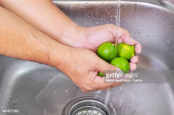 Cropped Image Of Hands Cleaning Lemons In Kitchen Sink