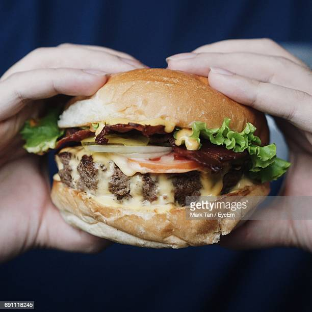 Cropped Image Of Hands Holding Burger