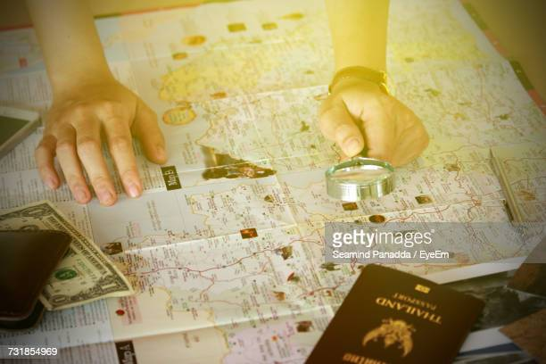 Cropped Image Of Hands Holding Magnifying Glass Over Map By Passport And Wallet With One Dollar Bill