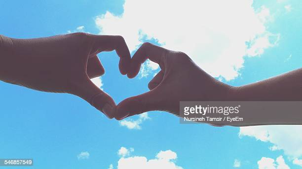 Cropped Image Of Hands Making Heart Shape Against Cloudy Blue Sky